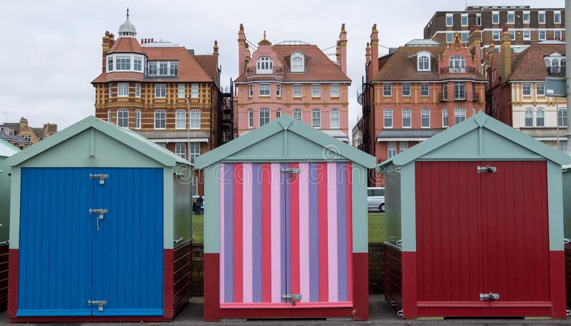 Colourful wooden beach huts on the sea front in Hove, Sussex, UK with blocks of flats behind. Colourful wooden beach huts, one painted in candy stripes, on the stock photo