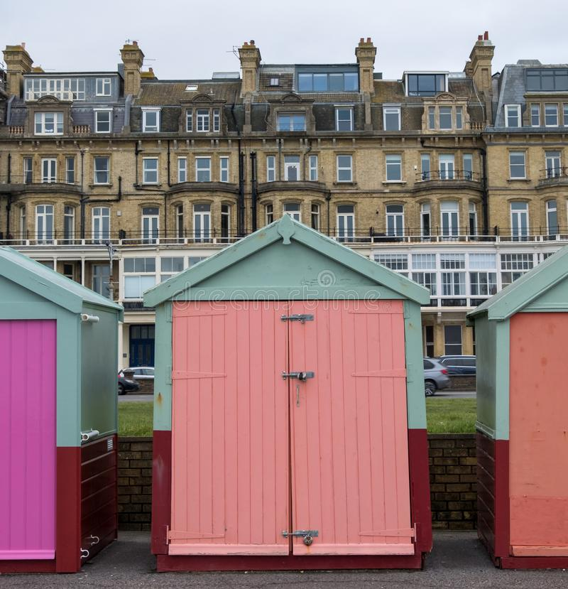 Colourful wooden beach huts on the sea front in Hove, Sussex, UK. Colourful wooden beach huts on the sea front in Hove, East Sussex, UK, with blocks of flats stock images
