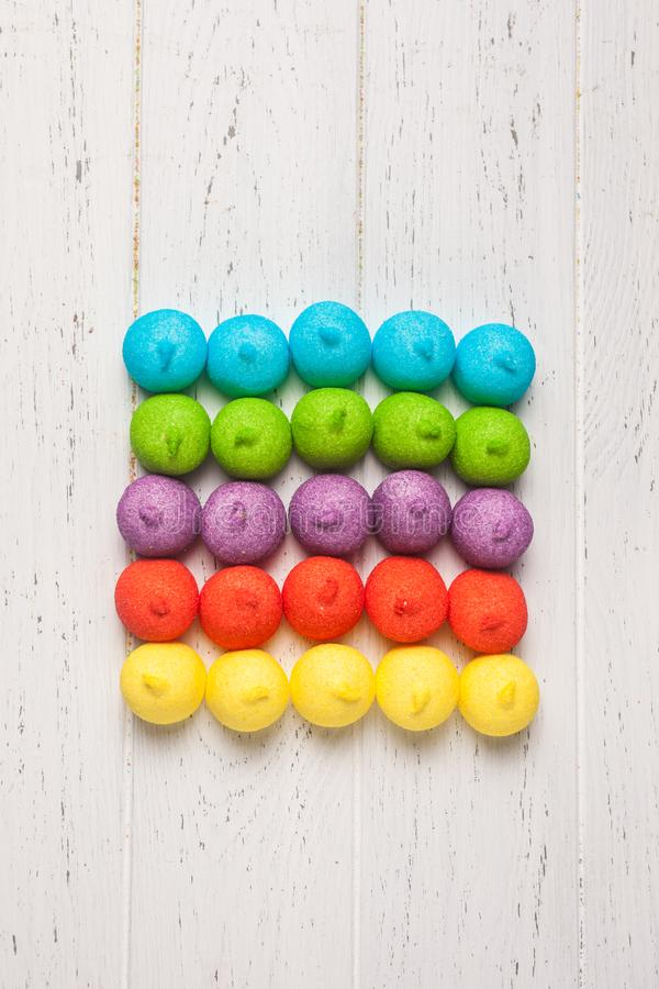 Colourful marshmallows with glitter effect. On white wooden background top view stock photo