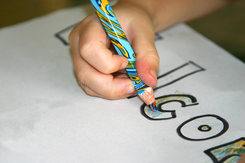 Colouring in. A closeup of a child colouring in with a coloured pencil stock images