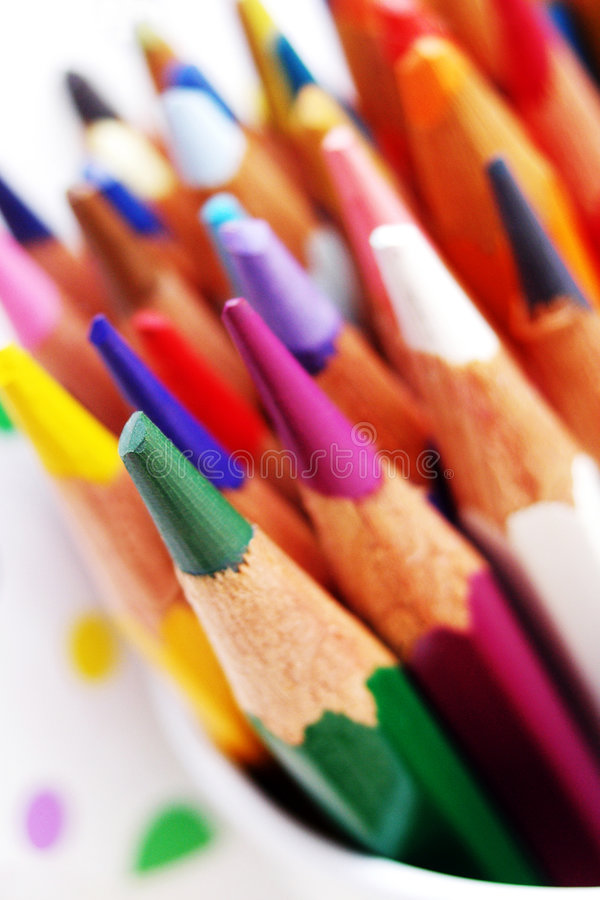 Colouring Palette of bright art pencils. Back to school ! - A bright colorful bunch of pencils form a fun pattern with one green pencil standing out in sharp royalty free stock photography