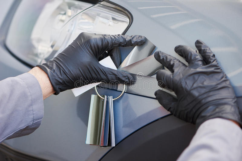 Colourist man selecting color of car with paint matching samples royalty free stock photography