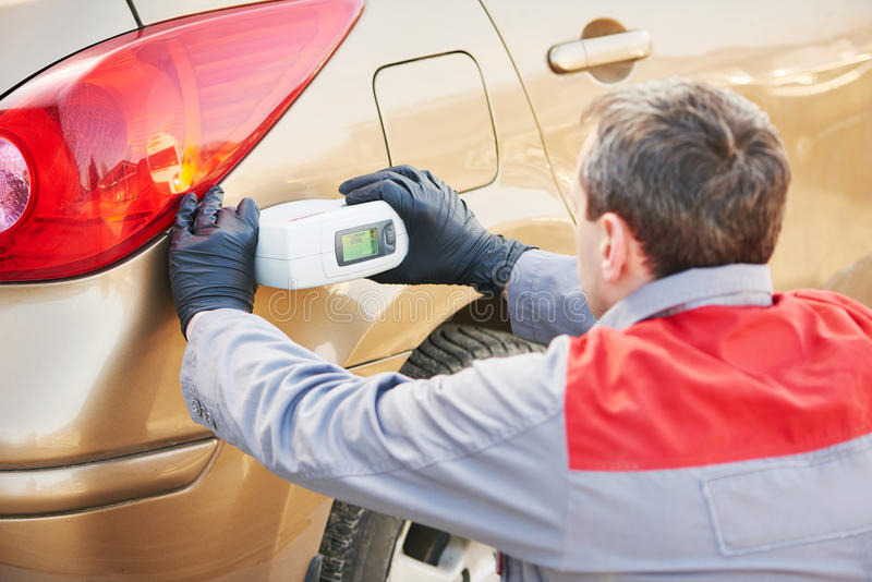 Colourist man selecting color of car with paint matching scanner royalty free stock images