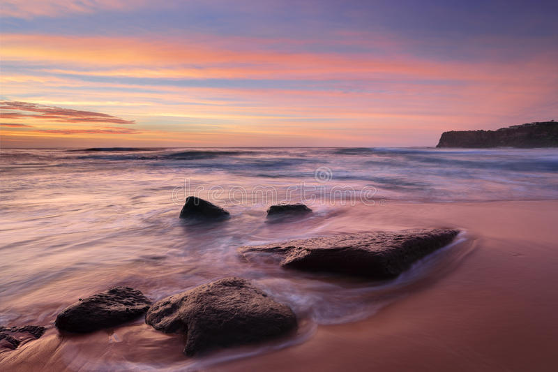 The colours of summer at Bungan beach Australia. Intense summer sunrise colours at Bungan Beach and mesmerising ocean flows. The beach is backed by 40m headland stock photography