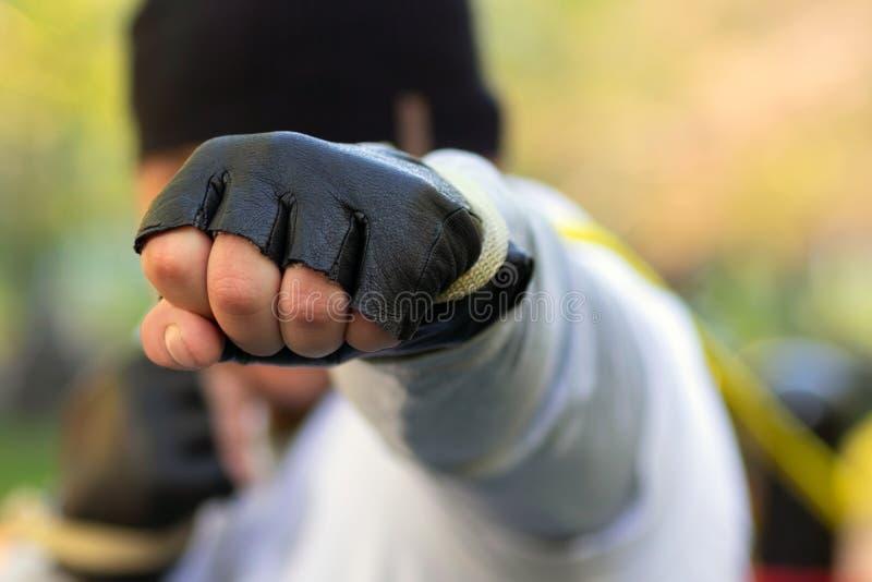 Colpi dell'uomo del pugile con il suo pugno in un guanto protettivo all'obiettivo In suo pugno premuto con grande gomma dall'istr immagini stock libere da diritti