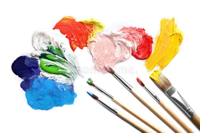 Colpi della pittura e spazzole differenti sulla vista bianca e superiore fotografia stock libera da diritti