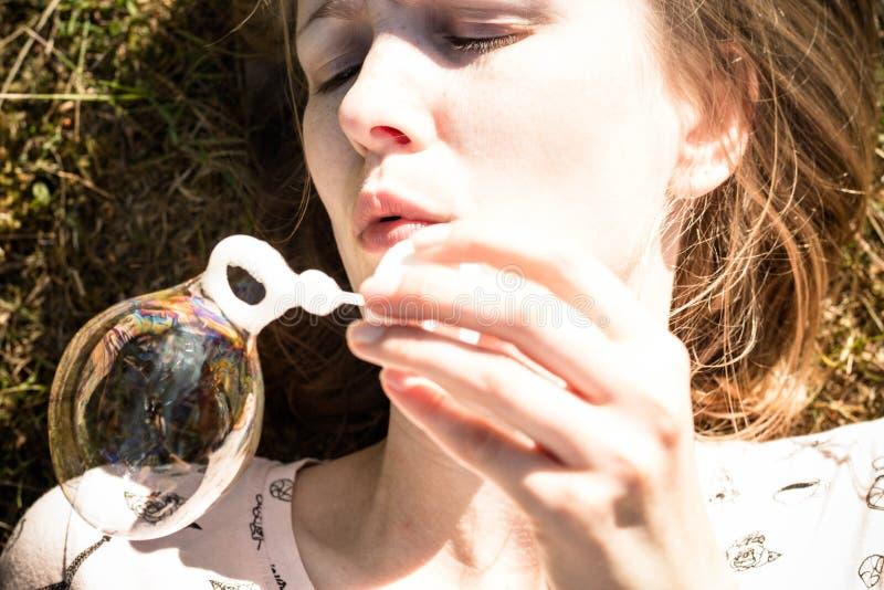 Colpi della ragazza ed i bei insaponano le bolle fotografia stock