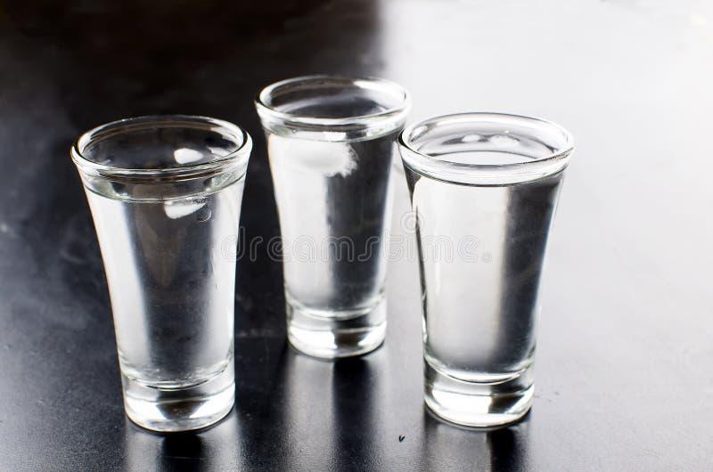 Colpi della vodka sulla tavola nera fotografie stock