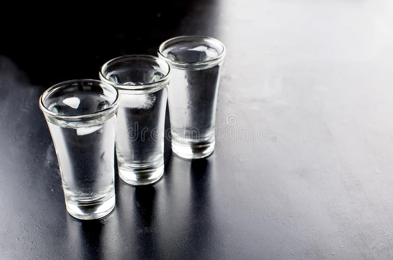 Colpi della vodka sulla tavola nera immagine stock libera da diritti