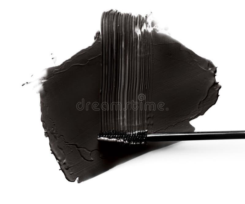 Colpi neri della spazzola della mascara del primo piano isolati su bianco fotografia stock