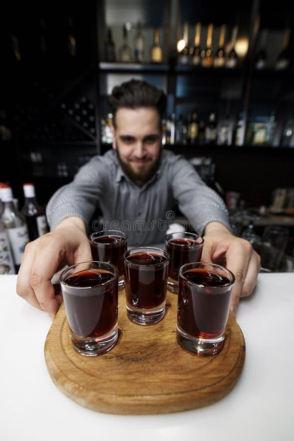 Colpi rossi alcolici su un bordo di legno fotografia stock libera da diritti