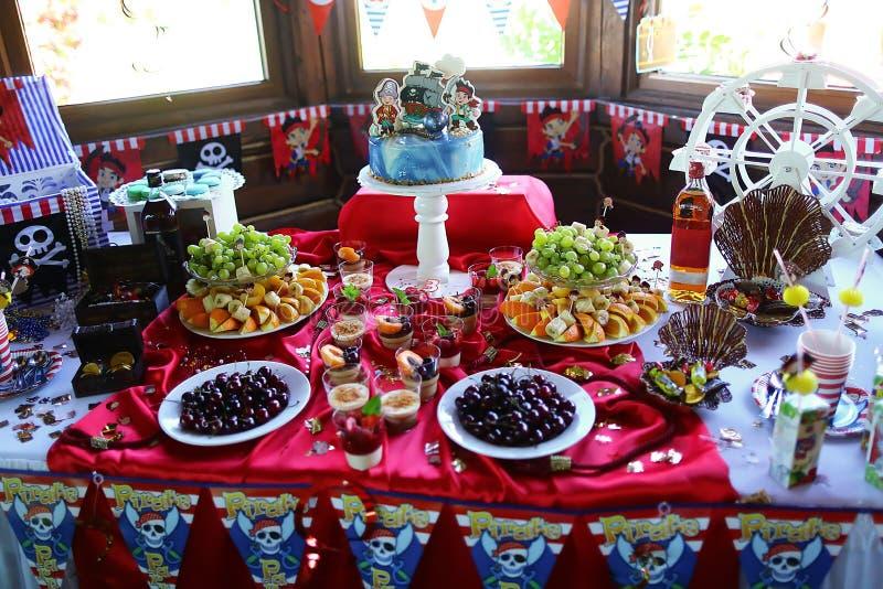 Colpisca il compleanno nei pirati di stile, la torta di compleanno, la frutta, i dolci, la caramella, biscotti dei bambini dei ma immagine stock