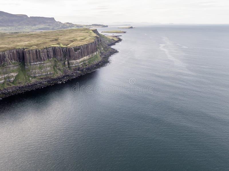 Colpo aereo cinematografico della linea costiera drammatica alle scogliere vicino alla cascata famosa della roccia del kilt, Skye immagini stock