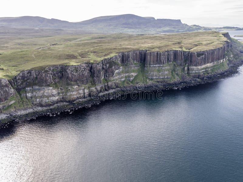 Colpo aereo cinematografico della linea costiera drammatica alle scogliere vicino alla cascata famosa della roccia del kilt, Skye fotografia stock