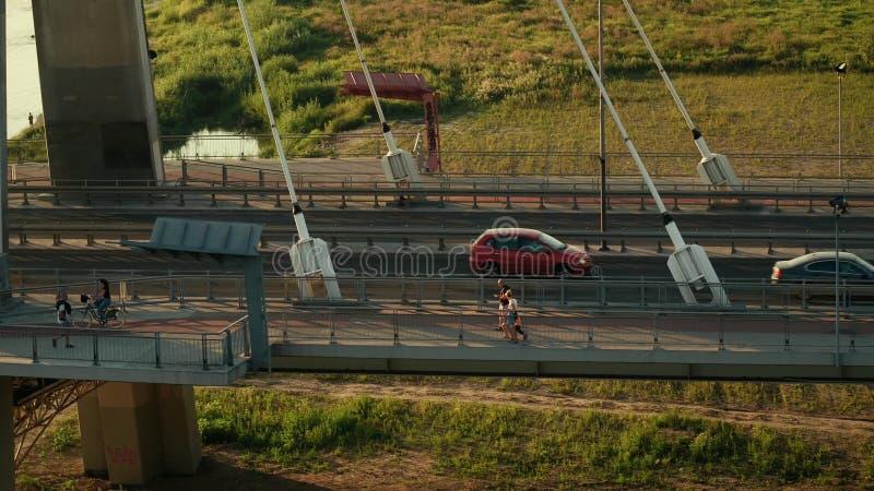 Colpo aereo dei ciclisti, del pedone e delle automobili muoventesi lungo il ponte guyed moderno sopra il Vistola immagine stock