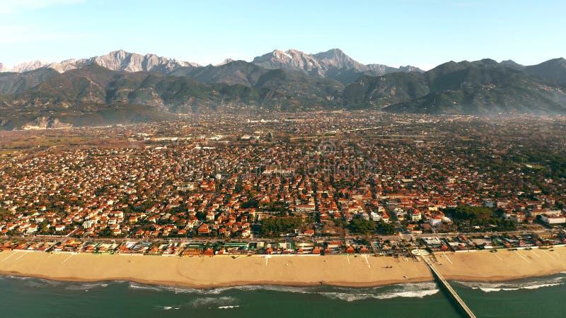 Colpo aereo delle montagne fronte mare e distanti pittoresche di Forte dei Marmi, Italia immagini stock