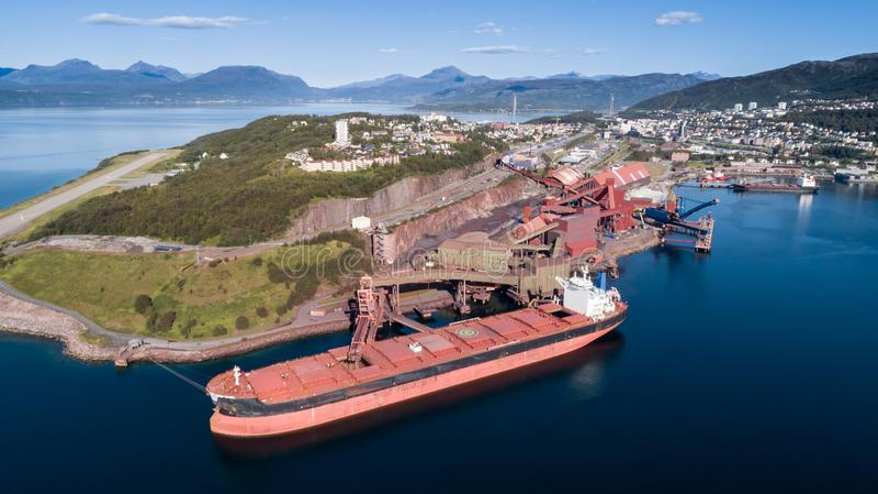Colpo aereo di una nave da carico che si ancora in terminale del porto e minerale di ferro di carico immagini stock