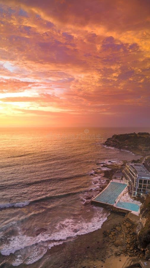 Colpo aereo di una spiaggia con una grande piscina di un hotel e del mare durante il tramonto fotografia stock libera da diritti