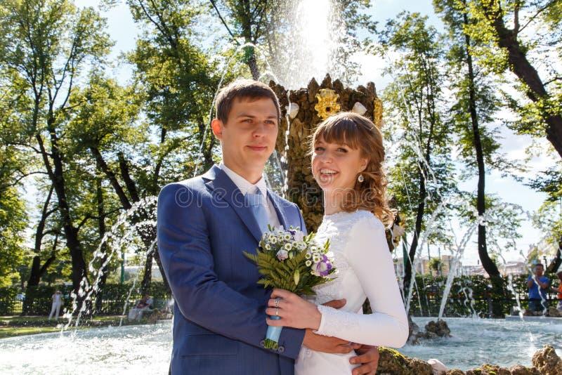 Colpo all'aperto della sposa e dello sposo che stanno fontana vicina in parco fotografia stock libera da diritti