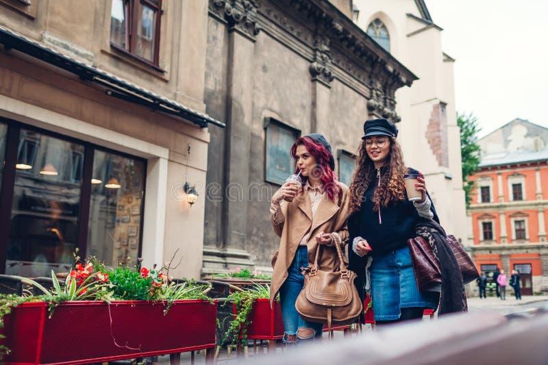 Colpo all'aperto delle giovani donne che camminano sulla via della città e mangiando caffè Amici che parlano e che si divertono immagini stock