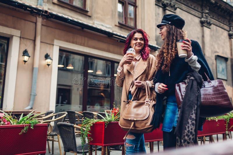 Colpo all'aperto delle giovani donne che camminano sulla via della citt? e mangiando caff? Amici che parlano e che si divertono fotografie stock libere da diritti