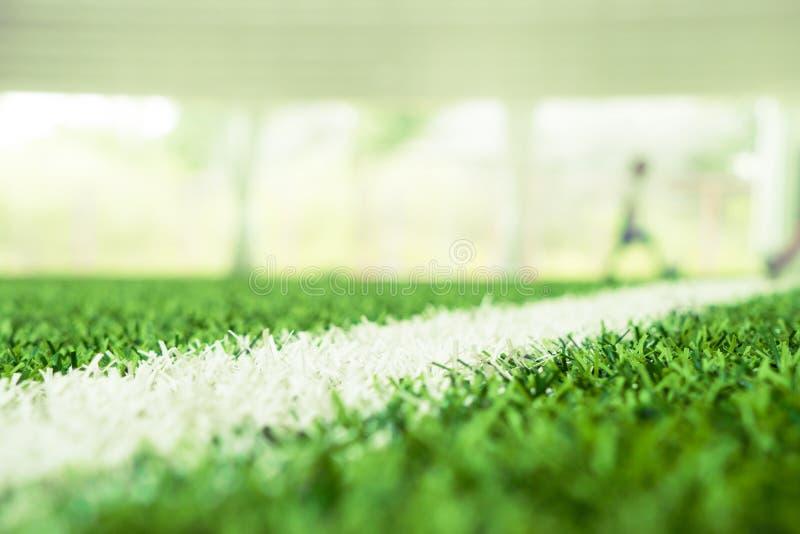 Colpo alto chiuso dell'erba di calcio con l'estratto della sfuocatura su fondo fotografie stock