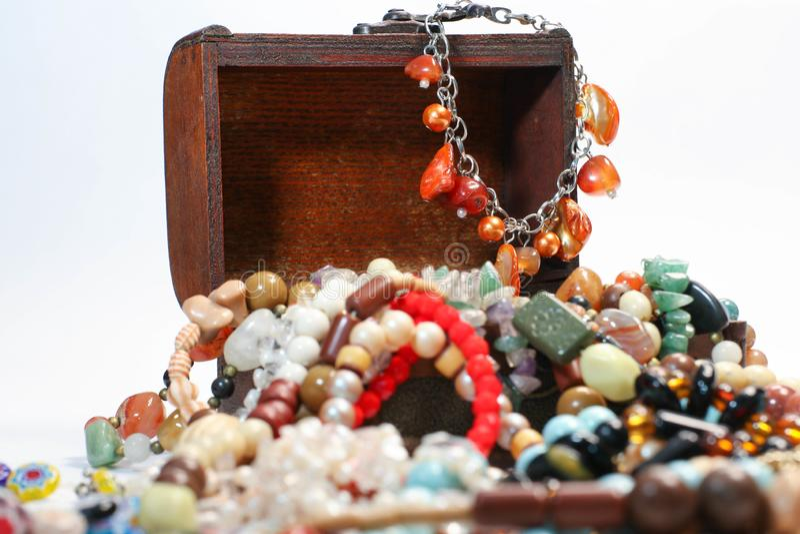 Colpo alto vicino del contenitore di legno di gioielli con le multi perle colorate su fondo bianco immagine stock libera da diritti