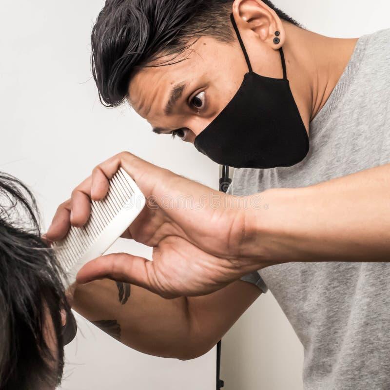 Colpo alto vicino dell'uomo che ottiene taglio di capelli d'avanguardia Cliente maschio del servizio del parrucchiere, facendo ta immagini stock libere da diritti