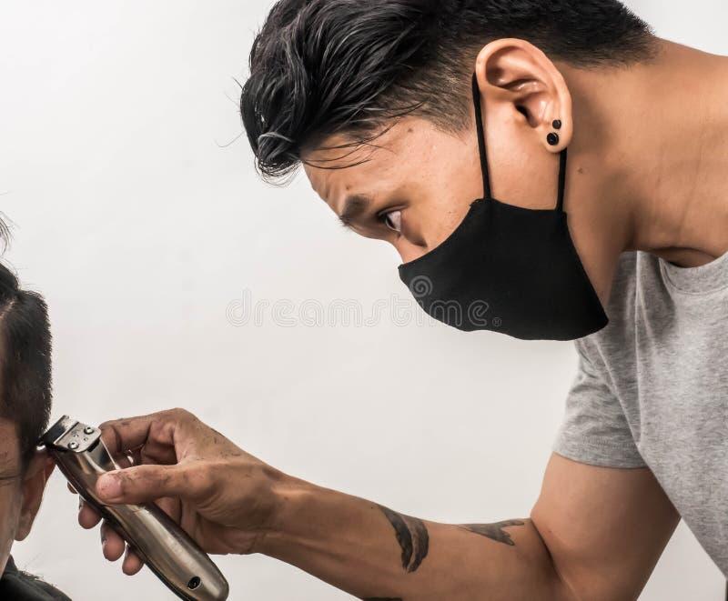 Colpo alto vicino dell'uomo che ottiene taglio di capelli d'avanguardia Cliente maschio del servizio del parrucchiere, facendo ta immagini stock