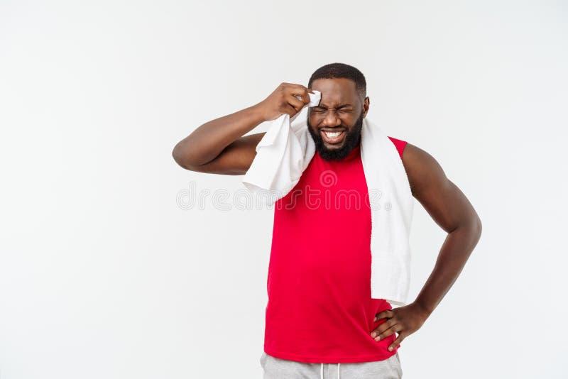 Colpo alto vicino di un uomo afroamericano stanco triste in abiti sportivi che puliscono il suo fronte con un asciugamano bianco, fotografia stock libera da diritti