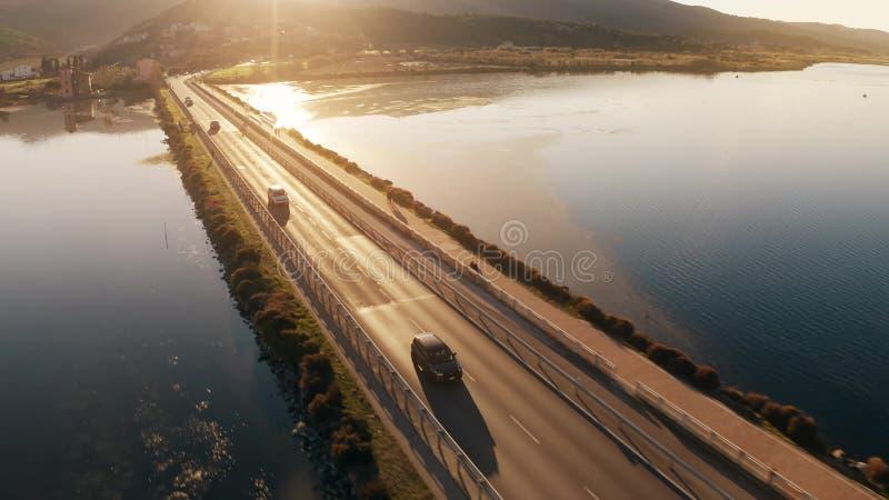 Colpo d'inseguimento aereo delle automobili sconosciute che si muovono lungo la diga in mare nella sera Orbetello, Italia fotografia stock