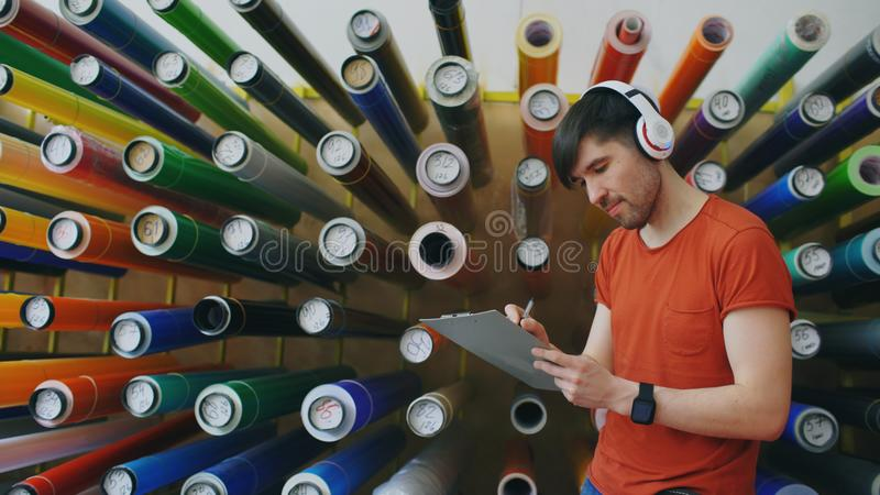 Colpo del carrello del giovane operaio felice in magazzino industriale che ascolta la musica e che balla durante il lavoro Uomo i fotografia stock libera da diritti
