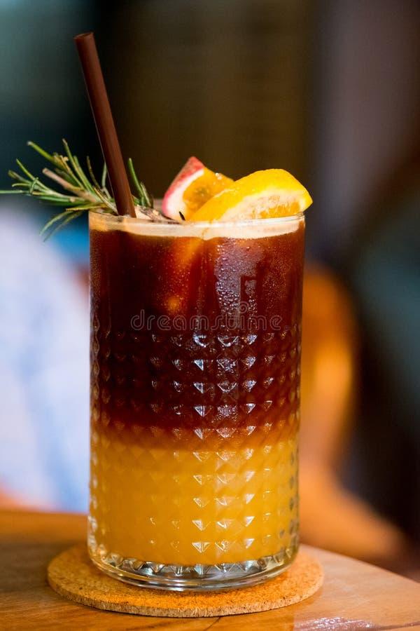 Colpo del preparato del caffè con il frutto della passione e l'arancia del succo in vetro immagine stock