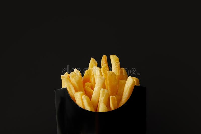 colpo del primo piano della scatola nera delle patate fritte deliziose isolate sul nero immagini stock libere da diritti