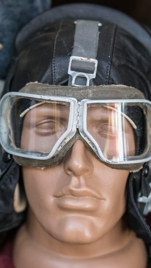 Colpo del primo piano della testa fittizia dell'uomo con il vecchi retro casco ed occhiali di protezione di cuoio pilota d'annata fotografie stock