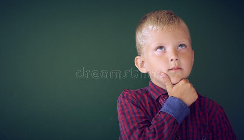 Colpo del primo piano dello scolaro che pensa con la mano sul mento isolato sulla lavagna Ritratto del bambino pensieroso che pen fotografia stock libera da diritti