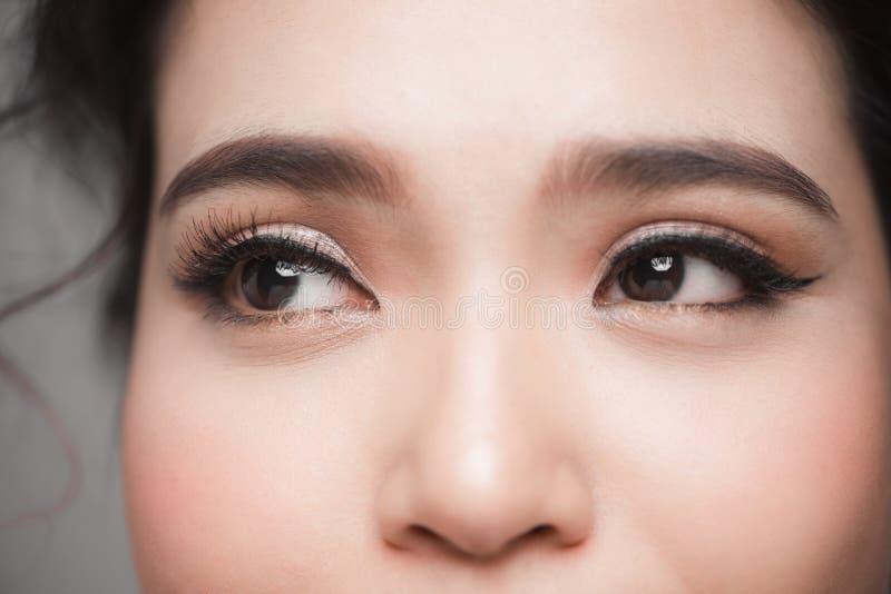 Colpo del primo piano di bello occhio asiatico della donna con i cigli lunghi fotografia stock