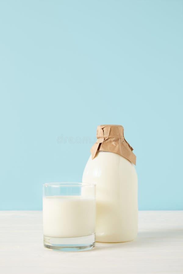 colpo del primo piano del vetro di latte e del latte in bottiglia avvolta da carta su fondo blu fotografie stock libere da diritti