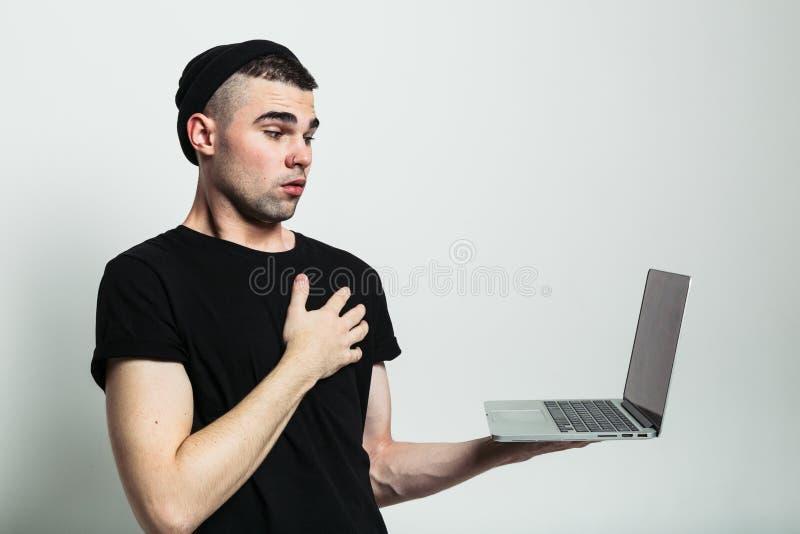 Colpo del tipo colpito che esamina computer portatile fotografie stock