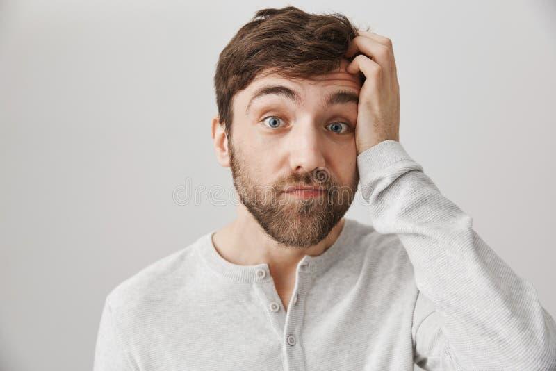 Colpo dell'interno del tipo attraente senza tracce ed imbarazzato con la barba sudicia, di graffio capo e di esame con le sopracc immagini stock libere da diritti