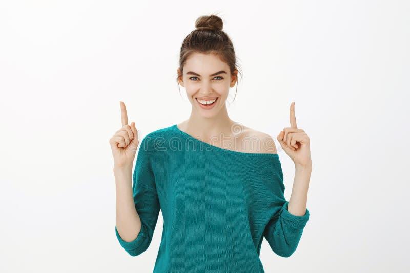 Colpo dell'interno della donna caucasica allegra amichevole in maglione sciolto verde, sorridente largamente ed indicante su, ess fotografia stock