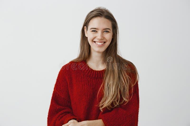 Colpo dell'interno della donna europea amichevole di aspetto affascinante in maglione sciolto alla moda, parlante con indifferenz immagine stock