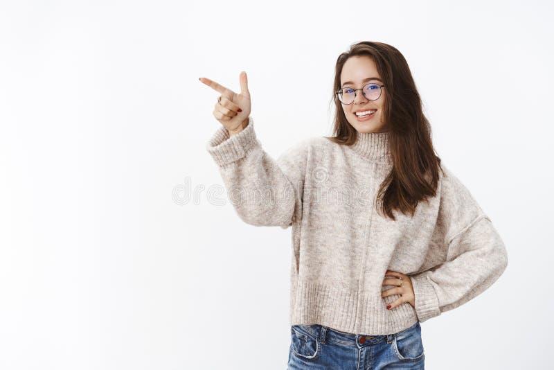 Colpo dell'interno della femmina attraente spensierata felice in vetri e mano della tenuta del maglione sulla vita, sorridente e  fotografie stock