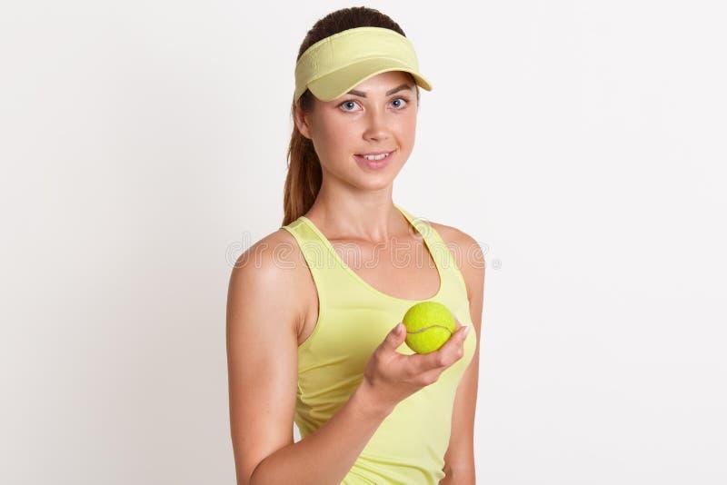 Colpo dell'interno dello studio di giovane fondo bianco controllante femminile magnetico positivo snello, tenente tennis giallo l immagine stock