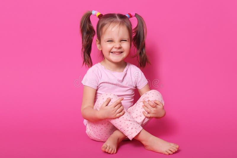 Colpo dell'interno dello studio di risata del bambino positivo che si siede sul pavimento, posare isolato sopra fondo rosa, magli fotografia stock