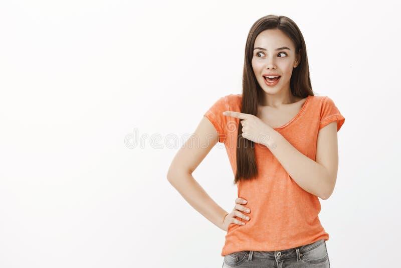 Colpo dell'interno di belle free lance femminili caucasiche emozionanti in maglietta arancio, discutente le voci ed indicante a s fotografie stock libere da diritti