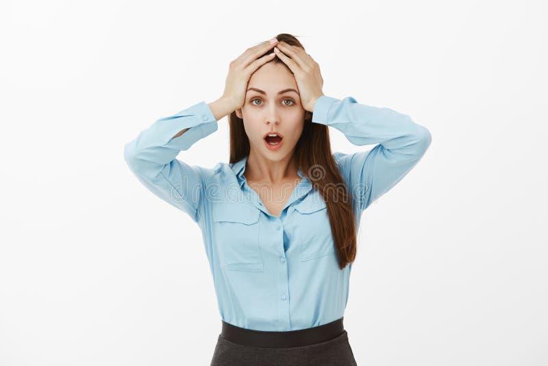 Colpo dello studio della donna di affari femminile impotente devastante che si tiene per mano sulla testa e sulla mandibola caden fotografie stock libere da diritti