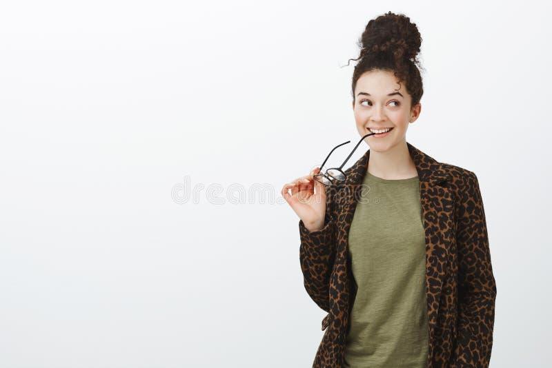 Colpo dello studio della ragazza urbana creativa vaga in cappotto del leopardo, orlo mordace dei vetri e di sguardo giusto con il immagini stock