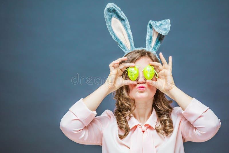 Colpo dello studio delle orecchie d'uso e di sostegno di un coniglietto della giovane donna felice dell'uovo di Pasqua variopinto immagini stock