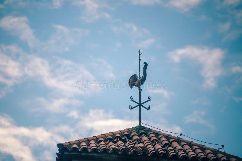Colpo di angolo basso di un supporto del tetto del gallo con il cielo nuvoloso nei precedenti al giorno immagine stock